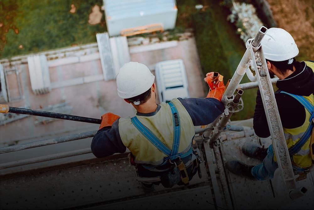 zwei Bauarbeiter mit Schutzhelmen stehen auf einem Gerüst und schauen nach unten