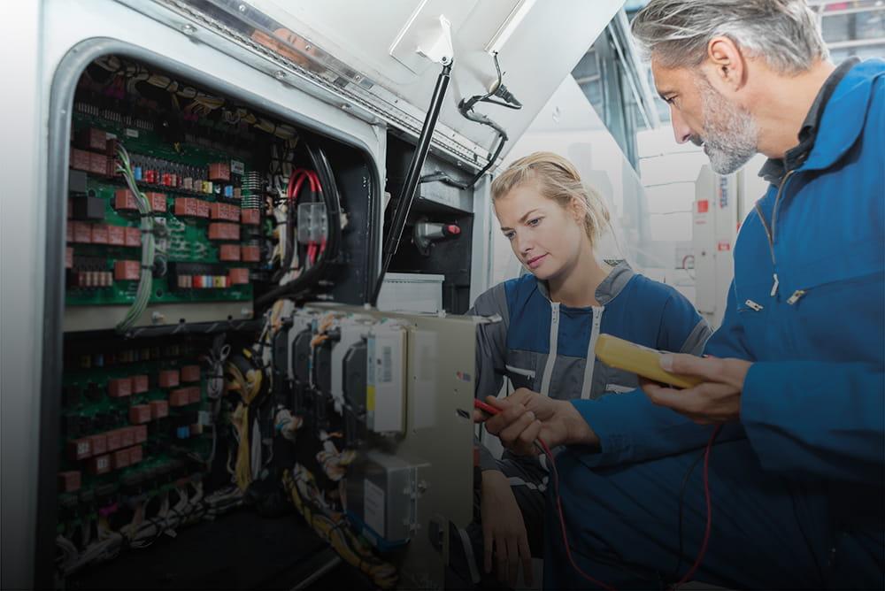 zwei Elektriker führen Arbeiten an einem Stromkasten durch