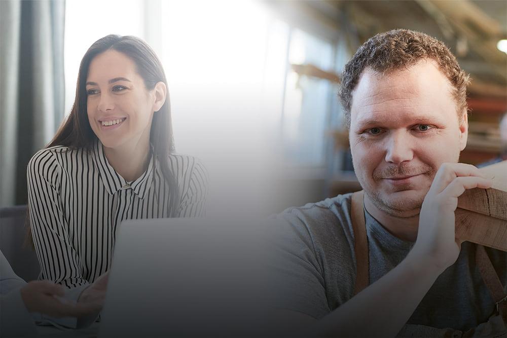 Frau sitzt am Laptop und unterhält sich und ein Handwerker trägt ein Holzbrett auf seiner Schulter