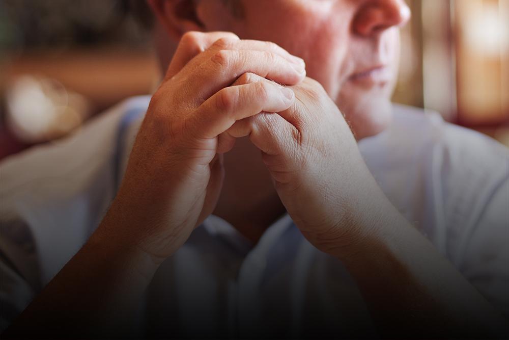 Mann sitzt mit aufgestützten Armen an einem Tisch und blickt zur Seite