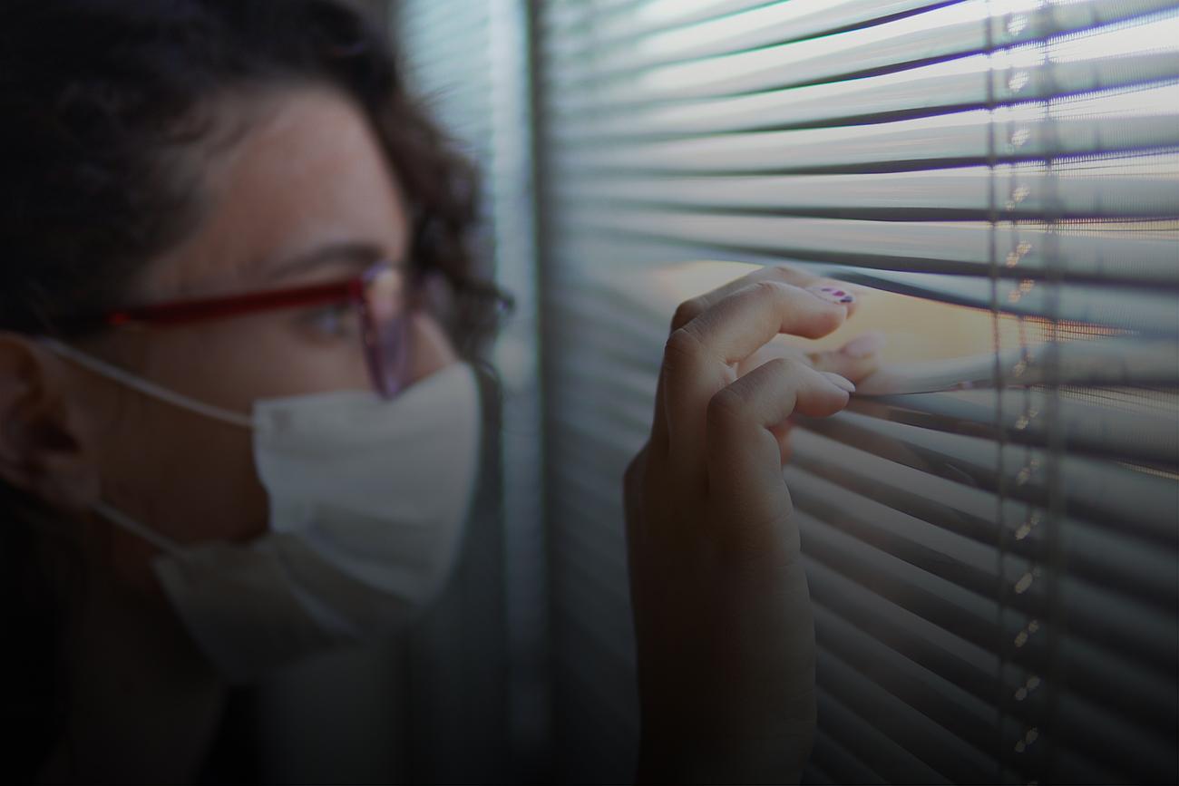 Frau mit Mund-Nasen-Schutz sieht durch eine Öffnung einer Jalousie