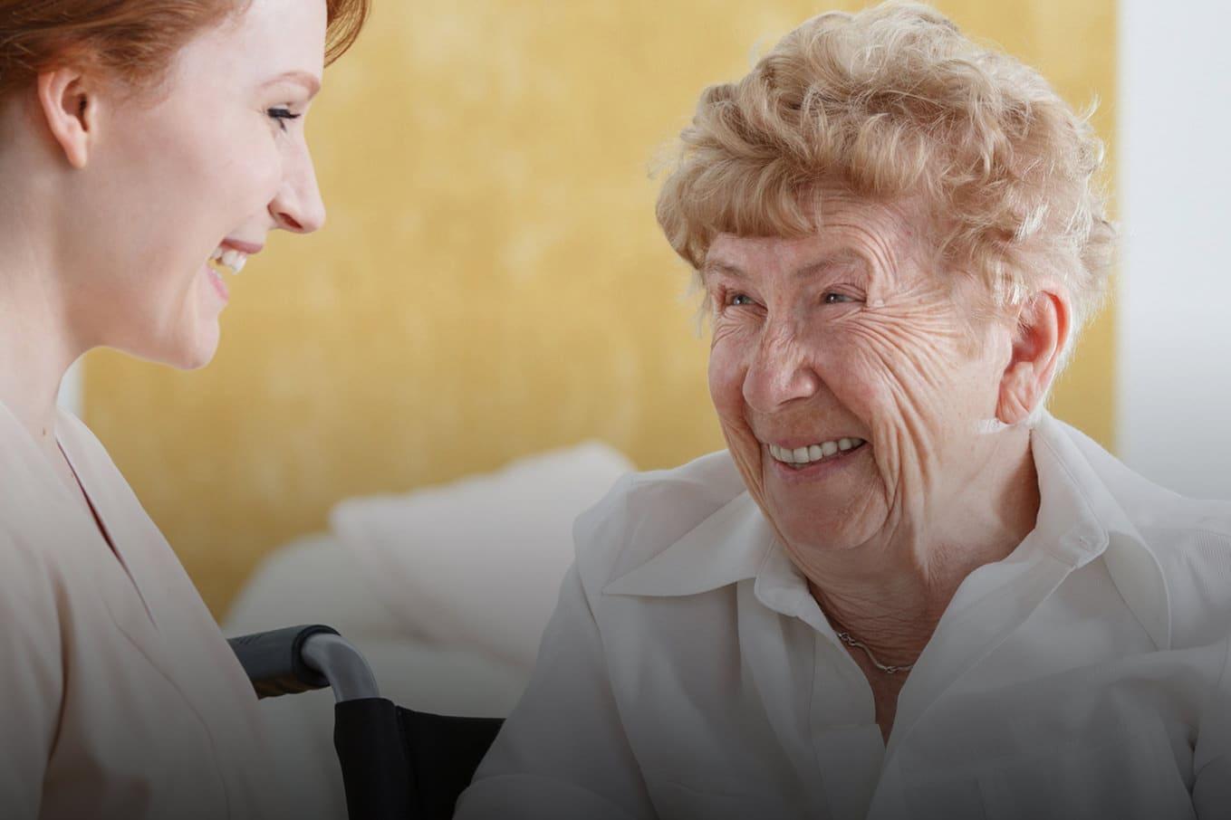 Rothaarige Pflegerin im Gespräch mit einer Seniorin im Pflegeheim