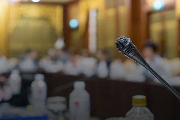 Mikrofon im Vordergrund, Veranstaltung verschwommen im Hintergrund